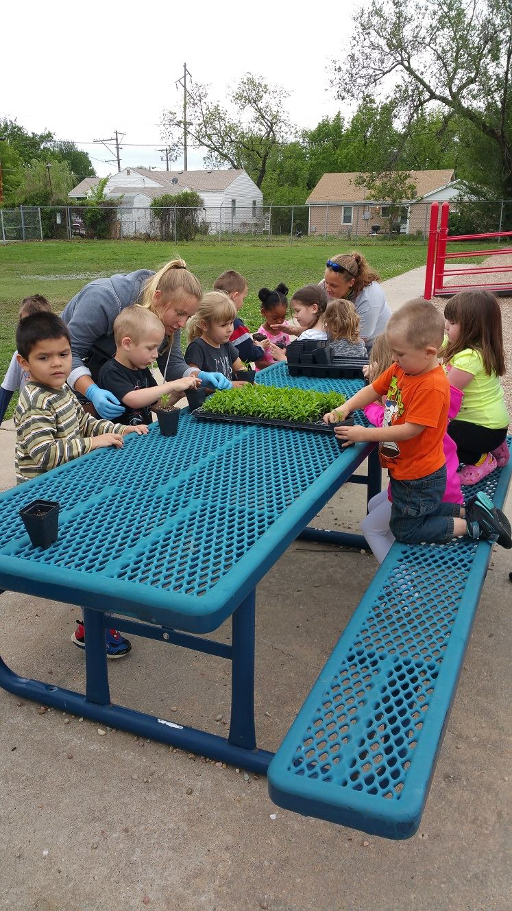 Kids sitting at a picnic table working with plants.